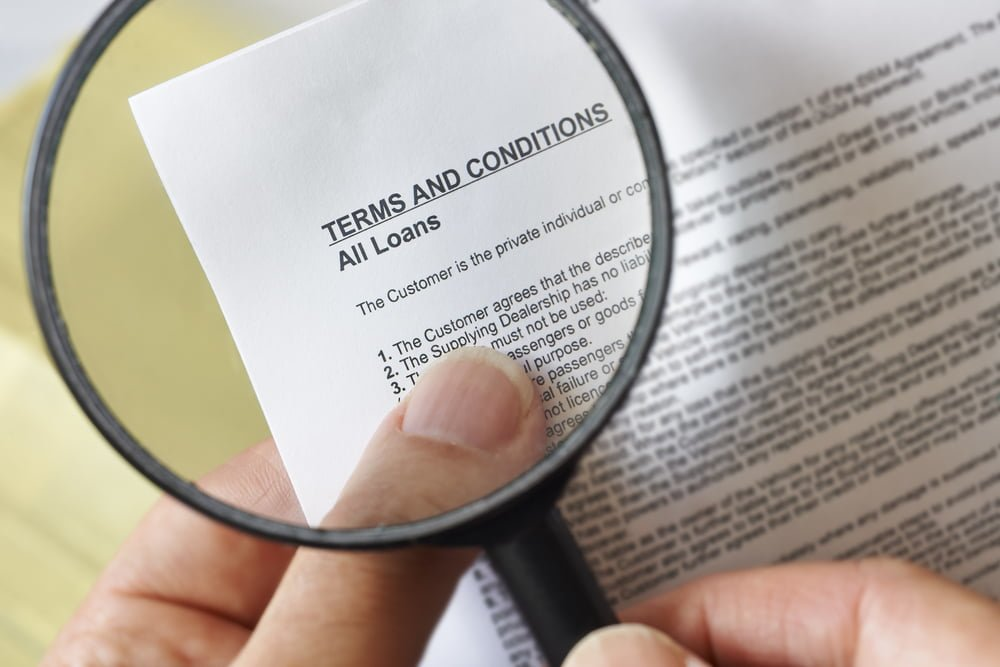 hands holding magnifying glass reading terms and conditions of loan agreement
