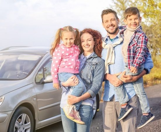 family in front of car